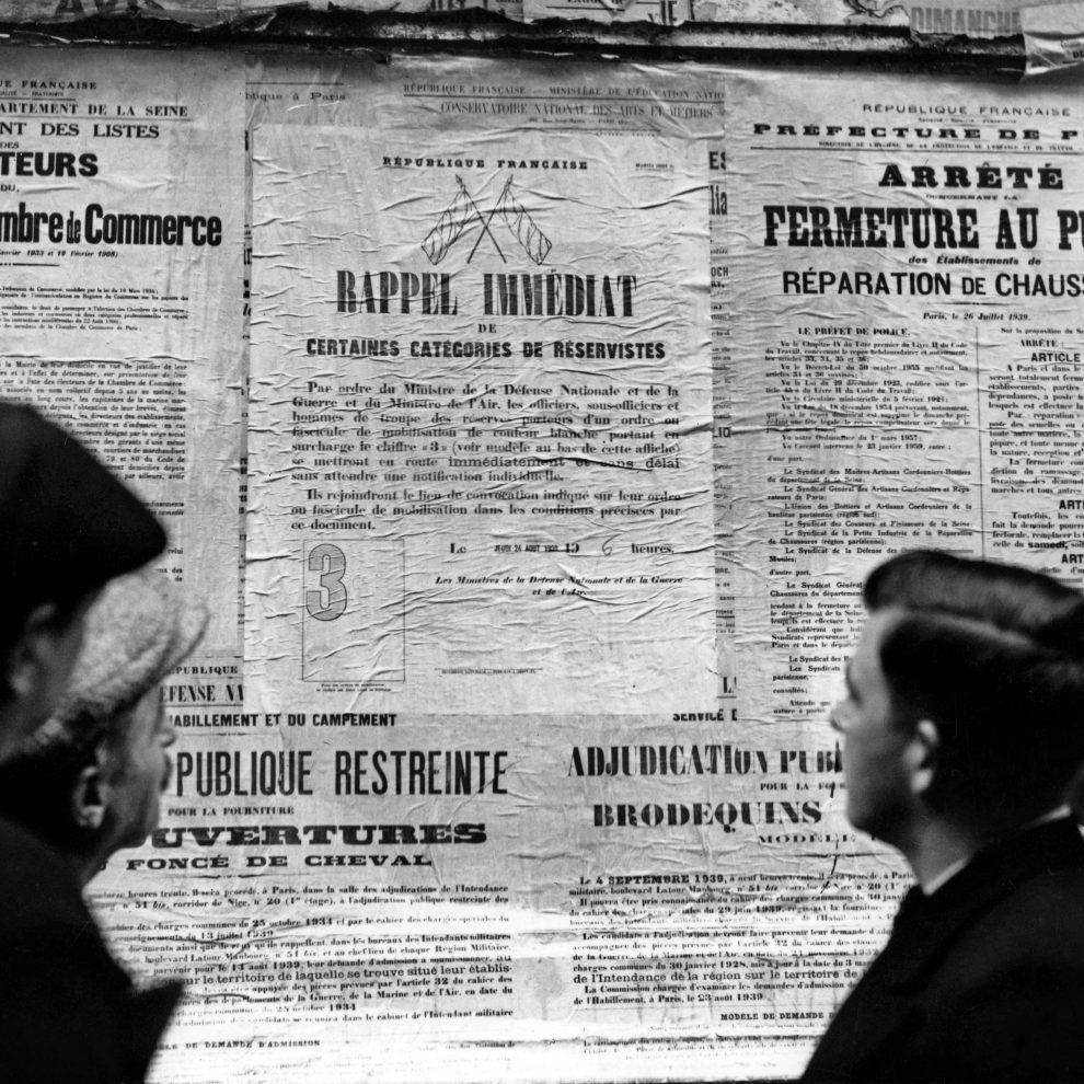 Passants devant les affiches du 24 août 1939 appelant à la mobilisation (rappel immédiat de certaines catégories de réservistes) Paris, France, août 1939.